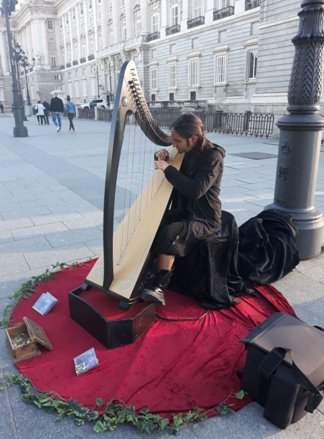 Spanish musician plays the harp outside Madrid's Royal Palace